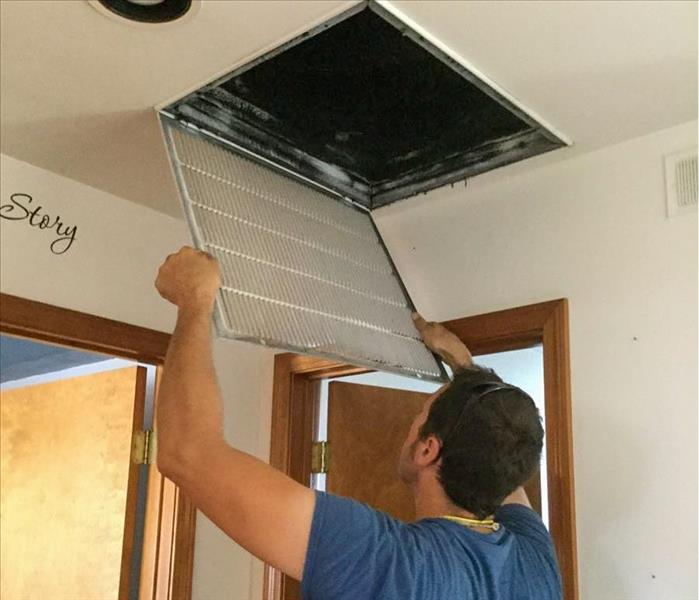 SERVPRO tech checking the air vent of a home